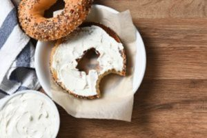 Bagels served on wood table and plate - one half with cream cheese and the other plain